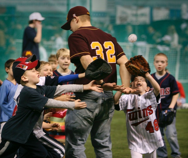 Children attending TwinsFest swarmed Gophers junior Chauncy Handran as they played home run derby with a whiffle ball on Saturday at the Metrodome. Ha