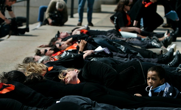 """Susan Montgomery of Minneapolis, center, and her son Dyvonte, 3, were among the 32 participants in a """"lie-in"""" outside the State Capitol to mark th"""