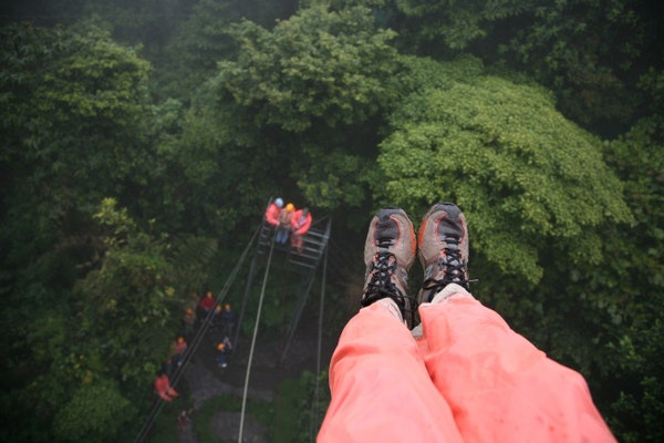 """Photographer's feet, 100 feet off the ground, looking down at the """"Tarzan Swing, 60 feet off the ground, at the Selvatura Zip Line in the cloud forest"""