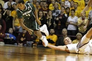 Michigan State's Keith Appling went after a loose ball as the Gophers' Colton Iverson grabbed his foot during the Spartans' 53-48 victory over t