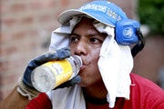 Daniel Garcia, 34, cools himself with water while wearing a t-shirt on his head to protect himself from a 90-degree heat while working his landscaping