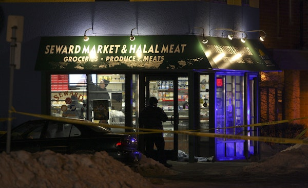 Police investigators examined the interior of the Seward Market on Jan. 6, 2010, after three people were shot and killed there.