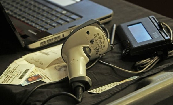 A voter ID scanning device made by Datacard Group. The system includes a scanner, left, digital signiture pad with stylus and a computer to input vote