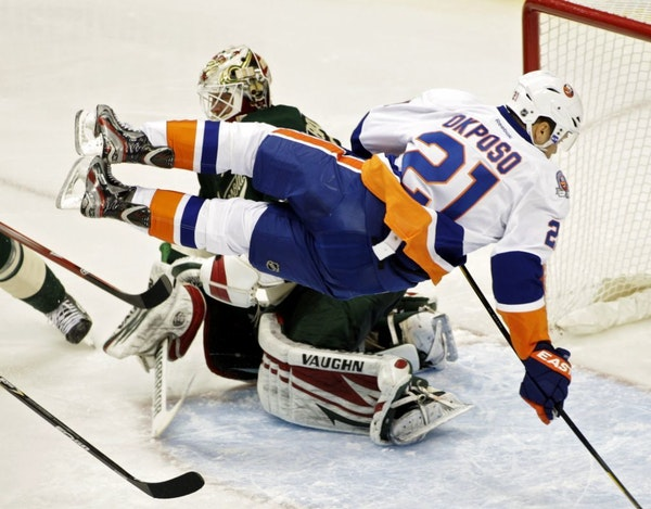 New York Islanders right wing Kyle Okposo (21) goes airborne as he skates in on Minnesota Wild goalie Niklas Backstrom (32), of Finland, during the th