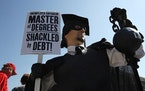 """In this Oct. 6, 2011 photo, Gan Golan of Los Angeles, dressed as the """"Master of Degrees,"""" holds a ball and chain representing his college loan debt du"""