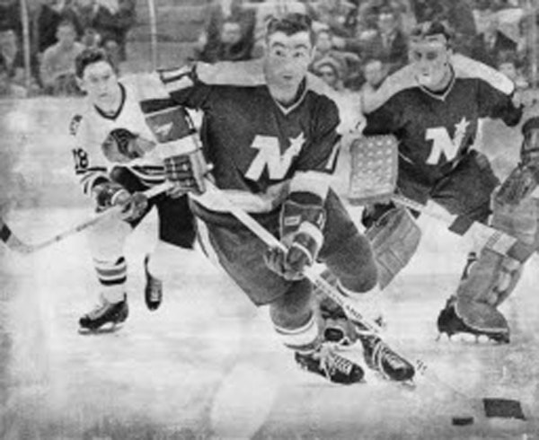 J.P. Parise carried the puck for the North Stars in 1970, with goalie Cesare Maniago looking on.