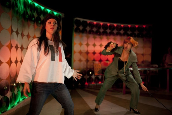"""Jamie Elvey, left, stars as Hanan, a Lebanese singer who surrenders her identity for Latin pop stardom, in """"Learn to Be Latina."""" Aditi Kapil plays an"""