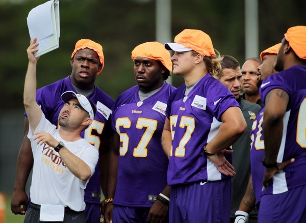 Vikings defensive assistant Jeff Imamura, left, held up plays for players to study during first day of practice Friday at Minnesota State Mankato.