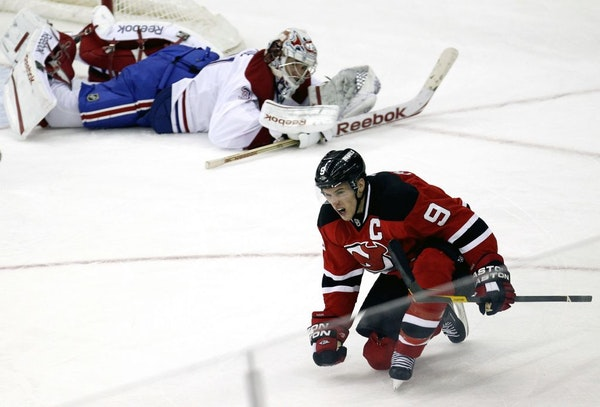 New Jersey Devils' Zach Parise (9) celebrates his goal as Montreal Canadiens goalkeeper Carey Price lays on the ice during the third period of an NHL