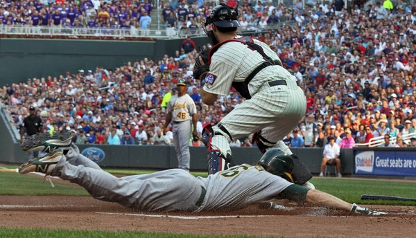 Oakland's Josh Reddick slid safely into home beating the throw to Twins catcher Joe Mauer for the first run of the ballgame in the first inning Saturd