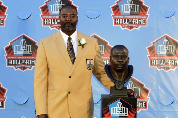 Former NFL player Chris Doleman poses with a bust of himself during an induction ceremony at the Pro Football Hall of Fame, Saturday, Aug. 4, 2012, in