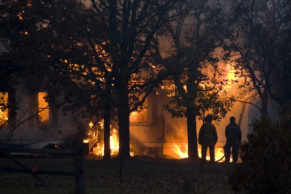 A fire consumes a house in Karlstad, Minn., Tuesday evening after wildfires fueled by high winds and dry conditions spread quickly.