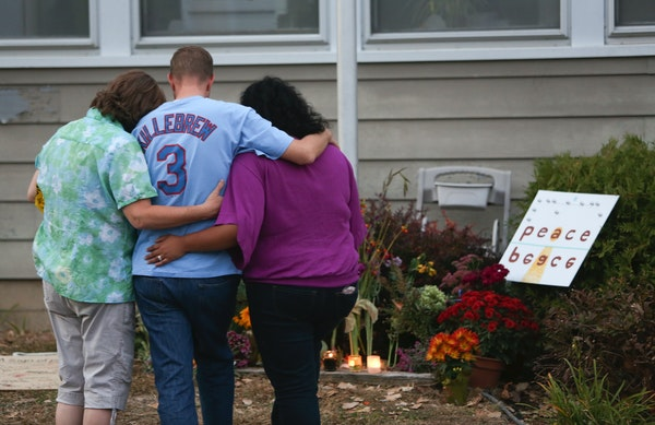 A family members of Ron Edberg consoled his son Dusty, center, in front of an informal memorial made for the victims in front of Accent Signage System