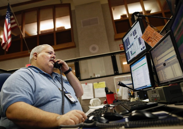 Gregers M. Nelson, senior shift supervisor at the Minneapolis Emergency Communications Center in City Hall, talked by phone to emergency personnel.