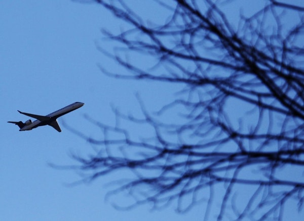 A plane that took off from MSP cruises over a Southwest Minneapolis neighborhood near the Crosstown and Oliver Ave. S Wednesday, Oct. 31, 2012, in Min