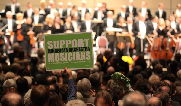 A packed audience gave a standing ovation, and held up a sign in support, to the musicians of the Minnesota orchestra at a concert held at the Minneap