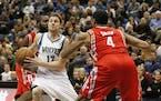 Minnesota Timberwolves guard Luke Ridnour (13) breaks through the defense of Houston Rockets guard James Harden, back left, and center Greg Smith (4)