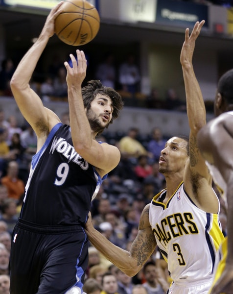 Timberwolves guard Ricky Rubio, left, passes over Indiana Pacers guard George Hill
