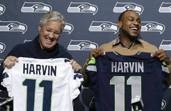 Seattle Seahawks' Percy Harvin, right, and coach Pete Carroll hold jerseys before a news conference at the NFL football team's headquarters Tuesday, M