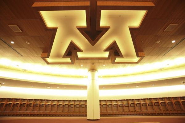 """The illuminated """"M"""" logo on the ceiling of the Gophers' locker room at the University of Minnesota."""