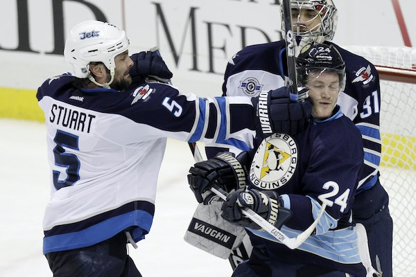 Jets defenseman Mark Stuart tried to clear Matt Cookke from in front of goalie Ondrej Pavelec during a Penguins victory in February.