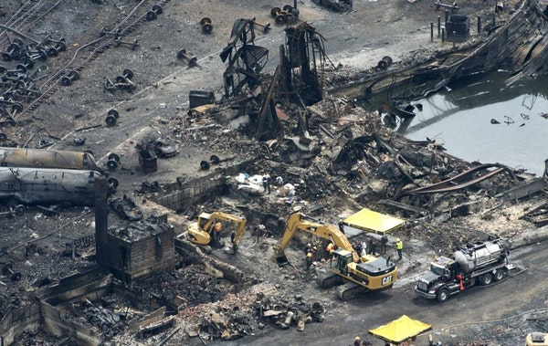 This aerial photo, workers comb through the debris after a train derailed causing explosions of railway cars carrying crude oil Tuesday, July 9, 2013