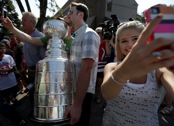 """A young fan took a """"selfie"""" as Nick Leddy of the Chicago Blackhawks passed by with the Stanley Cup at Maynard's in Excelsior on Thursday."""