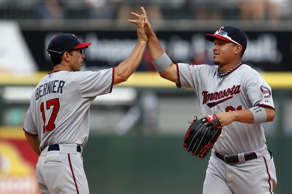 Minnesota Twins shortstop Doug Bernier (17) and left fielder Oswaldo Arcia (31) celebrate after they defeated the Chicago White Sox in a 5-2 victory i