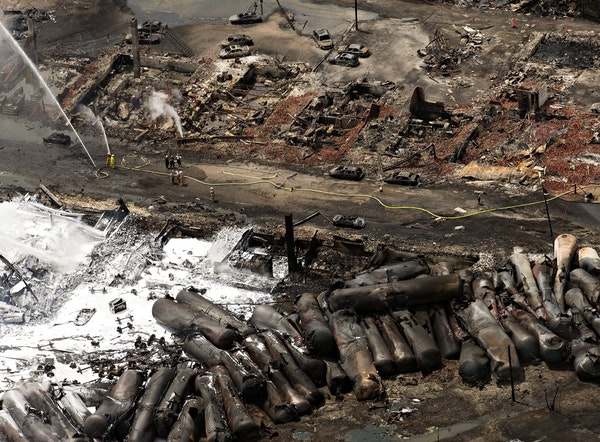 The downtown core lays in ruins as fire fighters continue to water smoldering rubble Sunday, July 7, 2013 in Lac Megantic, Quebec. A runaway train der