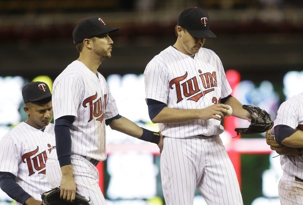 Minnesota Twins pitcher Kevin Correia, right, gets a consoling pat from third baseman Trevor Plouffe as he waits to be taken out in the seventh inning