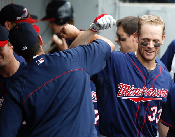 In this file photo, Twins' Justin Morneau (33) celebrates his home run with Chris Colabello in the dugout during the ninth inning of a baseball game a