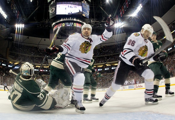 Chicago's Patrick Sharp celebrated with teammate Michal Handzus after he beat Wild goalie Josh Harding for a 1-0 Blackhawks lead on Tuesday night at X