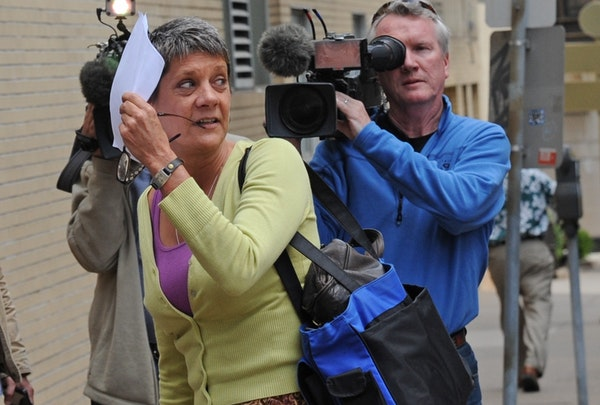 Lori Christensen tried to hide from the news media behind a sheet of paper.