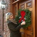 Krista Wolter puts a wreath on the front door of her listing in North Oaks.