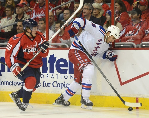New York Rangers left wing Taylor Pyatt (14) works the puck along the boards against Washington Capitals defenseman Nate Schmidt (88) in the first per