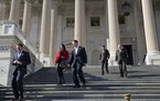 Members of the House of Representatives leave during a series of votes on a measure to let insurers keep offering health coverage that falls short of