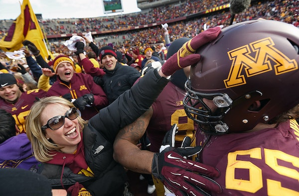 Offensive lineman Josh Campion and other Gophers players were greeted by enthusiastic fans on the field following the school's first victory over Ne