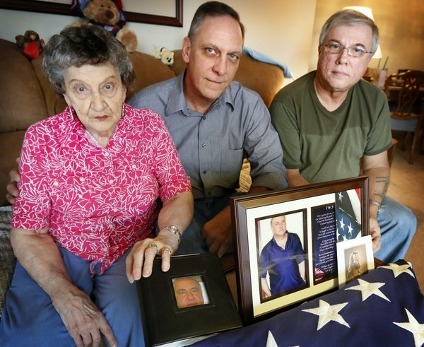 Elaine Bain and her sons Dick and Jim Bain, pose with pictures of her son, Jerry, who died of a drug overdose at the Minneapolis Veterans Home.