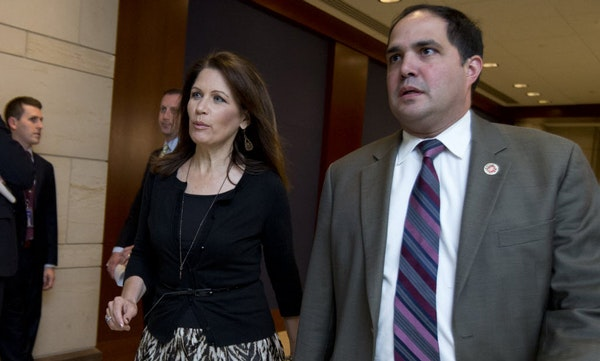 June 11, 2013: Rep. Michele Bachmann, R-Minn., arrives with staff member Javier Sanchez, right, for a closed all-member briefing on the NSA on Capitol
