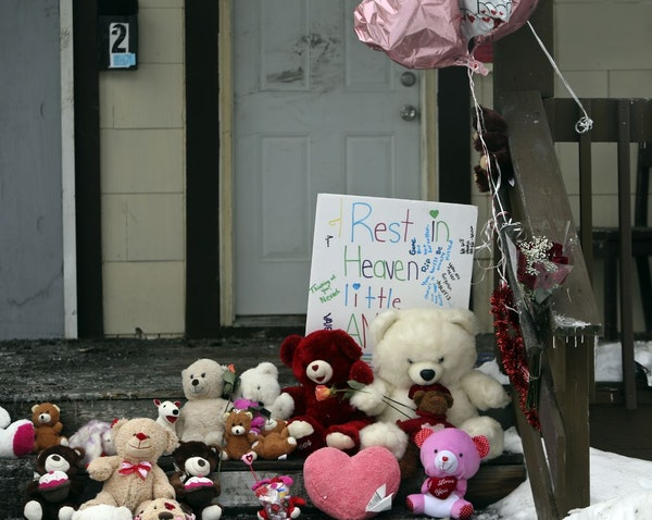 A day after the fire that took the lives of five, including three children, a growing collection of stuffed toys blocks the steps of the charred duple
