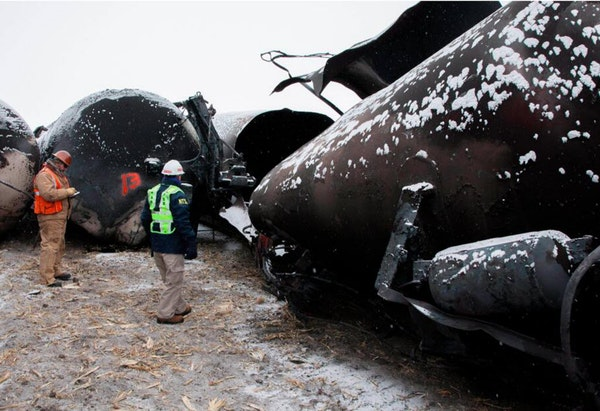 National Transportation Safety Board member Robert Sumwalt, right, views damaged rail cars in Casselton, N.D.