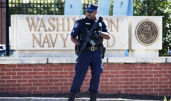 An armed Defense Department officer stood guard at the gate at the Washington Navy Yard the day after a 2013 attack.
