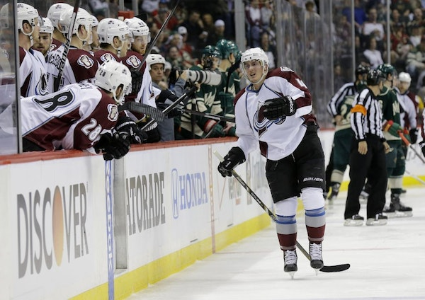 Colorado Avalanche defenseman Tyson Barrie, right, leaves the ice after getting injured on a hit by Minnesota Wild left wing Matt Cooke during the sec