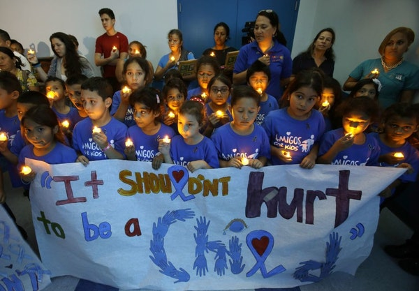 Children from an after school program participate in a candlelight vigil commemorating National Child Abuse Prevention Month at Jose Marti Park in Mia