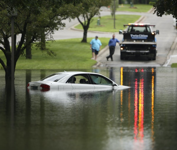 A tow truck waited to remove a car that was partially submerged on Kings Highway next to Lakewood Cemetery in Minneapolis Thursday afternoon.