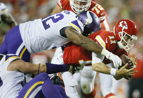 Kansas City quarterback Alex Smith did well to hang on to the ball while being dragged down by Vikings defensive tackle Tom Johnson (92) in the second