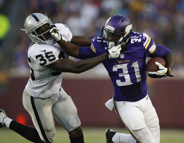 Minnesota Vikings running back Jerick McKinnon (31) stiff armed Oakland Raiders defensive back Chimdi Chekwa (35) as he made a two yard gain in the se