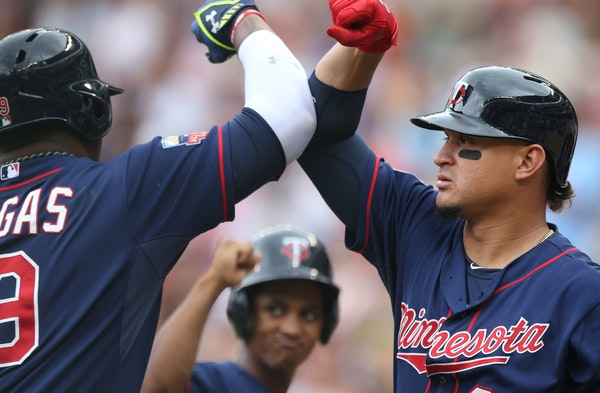 Minnesota Twins' Oswaldo Arcia, right, gives an elbow bump to Kennys Vargas as a ball boy, center, waits his turn after Vargas hit a solo home run off