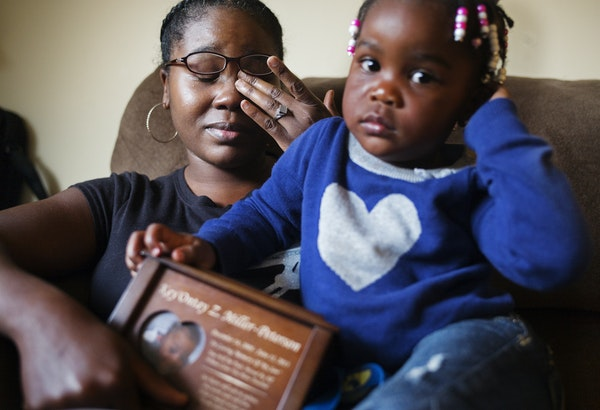 Ashia Miller (with daughter Julianna, 2) held her nephew Ke'Ontay's urn. Family members said they made 25 to 30 reports that the boy was being abused.