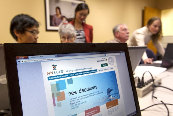 In this Dec. 21, 2013 file photo, navigators help Minnesotans sign up for MNsure health benefits before the deadline for coverage during all-day small